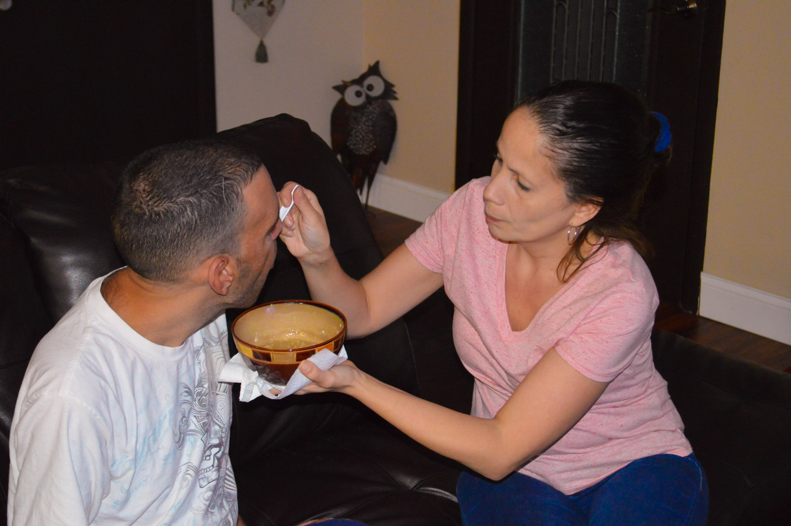 Group home staff member feeding resident with developmental disability
